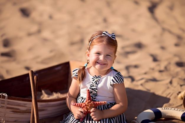 Babymeisje zittend in een boot, verkleed als zeeman, op een zandstrand met schelpen aan zee Premium Foto