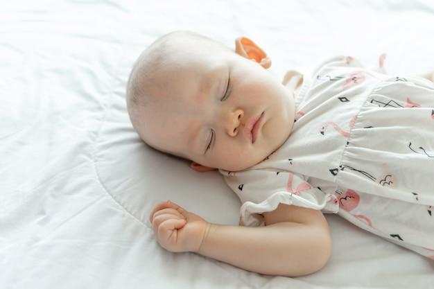 Babyslaap op een wit bed Gratis Foto