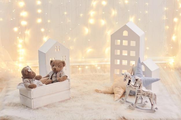 Babyspeelgoed en stuk speelgoed huis op een achtergrond van kerstmislichten. vakantie inrichting Premium Foto