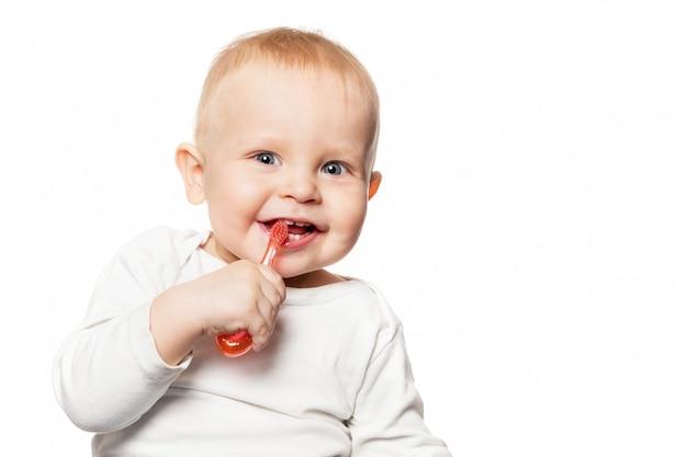 Babytanden zorgen. glimlachende jongen die zijn tanden met een tandenborstel voor zuigeling borstelt. Premium Foto
