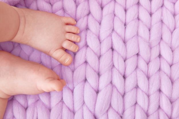 Babyvoetjes op een grote gebreide lila deken. wenskaart voor een baby shower, bevalling, zwangerschap. copyspace. Premium Foto