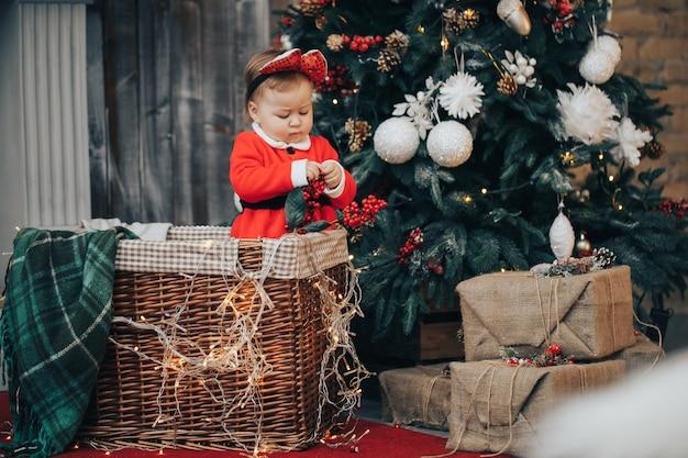 Babyvrouw die op vloer met kerstmisbal kruipen die de hoed en het kostuum van de kerstman over lichten dragen bij achtergrond Premium Foto