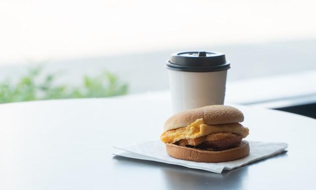 Bacon en omelet hamburger op het papier met witboek koffiemok op de tafel in fastfoodrestaurant Premium Foto