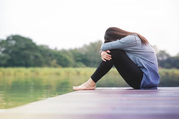 Bad day concept. verdriet vrouw zittend door de rivier op houten terras dek Premium Foto