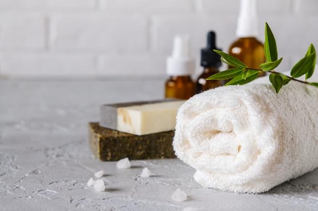 Bad en natuurlijke cosmetica concept. met de hand gemaakte zeepstaven en handdoeken op witte lijst. spa- en lichaamsverzorging Premium Foto