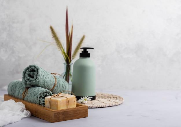 Badconcept met zeepfles en handdoeken Gratis Foto