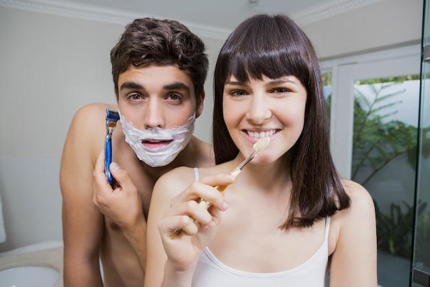 Badkamerroutine voor gelukkig jong stel tanden poetsen en scheren in spiegel Premium Foto