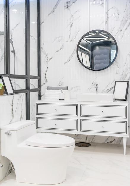 Badkamersbinnenland met witte muur, uitstekend meubilair, handdoeken, toilet en gootsteen Premium Foto
