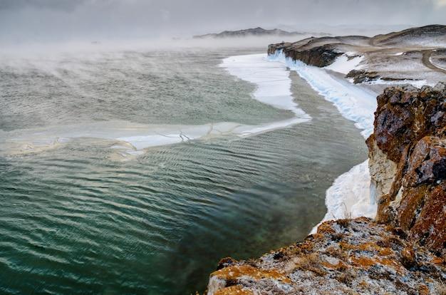 Baikal lake en rock in de koude december. tijd van bevriezing. ijsschotsen zwemmen op het water Premium Foto