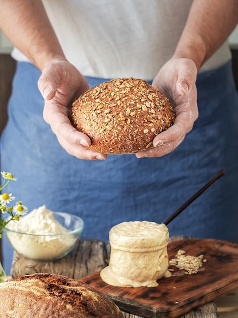 Baker houdt zelfgemaakt ambachtelijk biologisch brood vers uit de oven Premium Foto