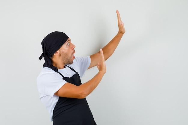 Baker man houden handen op beschermende wijze in t-shirt Gratis Foto