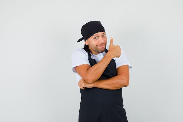 Baker man in t-shirt, schort duim opdagen en blij kijken Gratis Foto