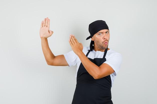 Baker man in t-shirt, schort met karate hakken gebaar en op zoek zelfverzekerd Gratis Foto
