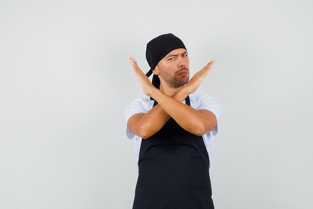 Baker man in t-shirt, schort met stopgebaar en resoluut op zoek Gratis Foto