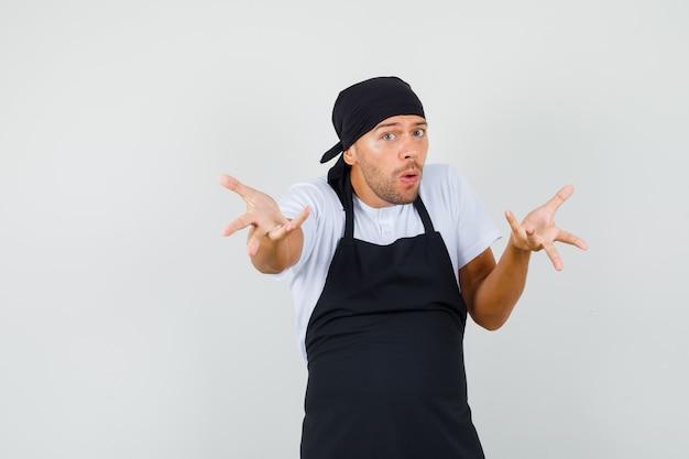 Baker man in t-shirt, schort strekken handen in vragend gebaar en op zoek verward Gratis Foto