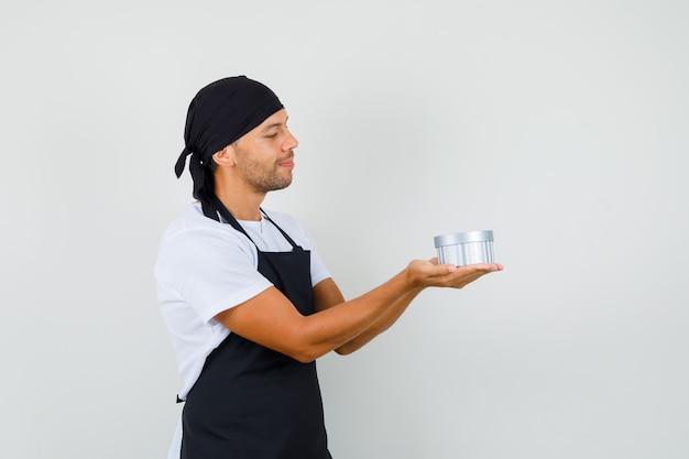 Baker man kijken naar geschenkdoos in zijn handpalmen in t-shirt Gratis Foto