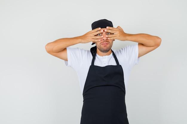Baker man kijkt door vingers in t-shirt Gratis Foto