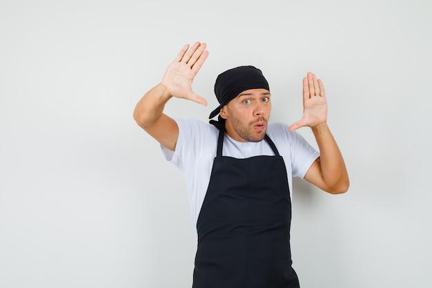 Baker man overgave gebaar maken in t-shirt Gratis Foto