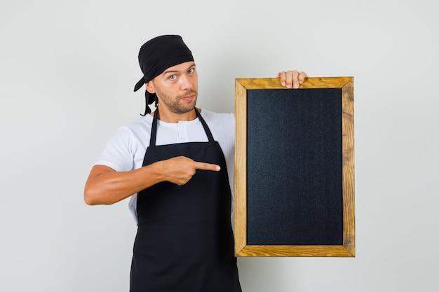 Baker man wijzend op bord in t-shirt Gratis Foto