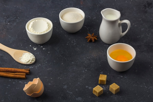 Bakken achtergrond. ingrediënten voor het koken van cake (meel, ei, suiker, melk) in kommen op donkere tafel. voedsel concept. bovenaanzicht, plat lay-out, kopieer ruimte voor tekst. Premium Foto