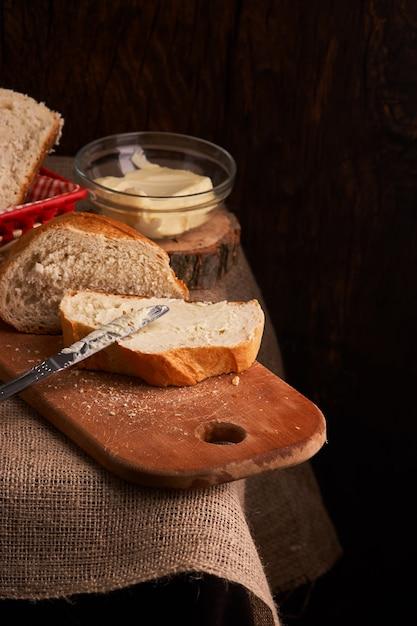 Bakkerij gouden rustieke knapperige broden en broodjes op zwarte bordachtergrond. stilleven van bovenaf vastgelegd Premium Foto