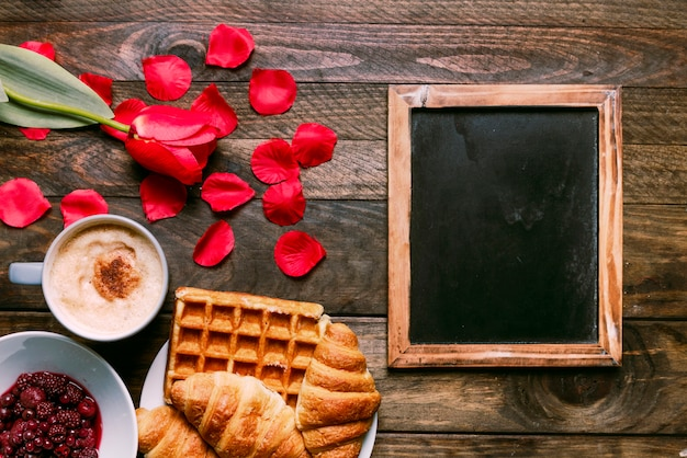 Bakkerij op plaat dichtbij kop van drank, bloem, jam, bloemblaadjes en fotokader Gratis Foto