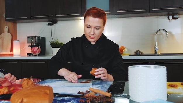Bakkerijarbeider die peperkoekkoekjes maken door ovenschaal te vullen met gebakjedeeg. Premium Foto