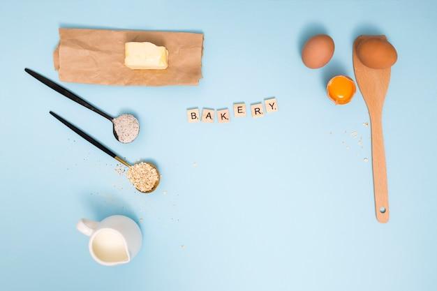 Bakkerijblokken met boter; melkkan; haver schuur; meel; eieren en houten spatel op blauwe achtergrond Gratis Foto