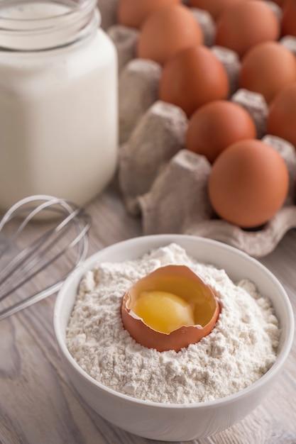 Bakkerijingrediënten - bloem, eieren, melk, dooier op een lijst. zoet gebak bakken concept. detailopname Premium Foto