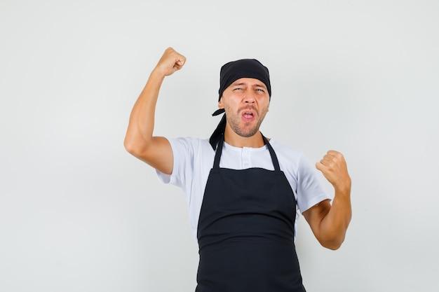 Bakkersman in t-shirt, schort die winnaargebaar toont en gelukkig kijkt Gratis Foto