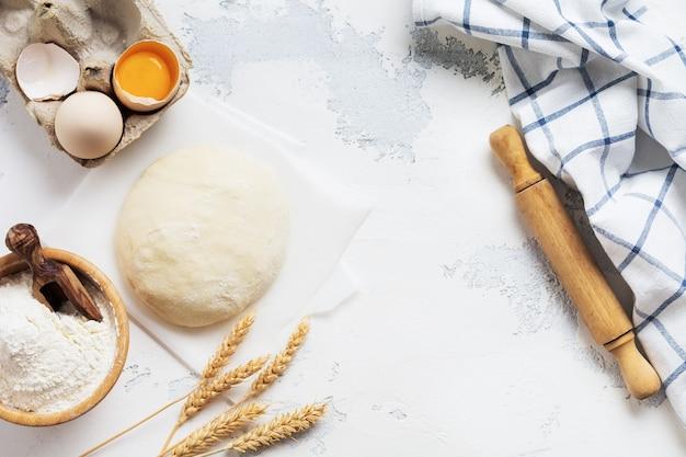 Bakmuur met deeg en ingrediënten voor de bereiding van deegwaren of pannenkoeken, eieren, bloem, water en zout op witte rustieke oude lijst. bovenaanzicht. Premium Foto