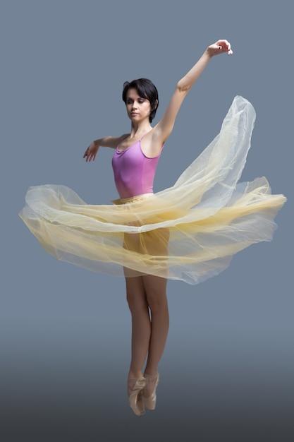 Ballerina danst in de studio op grijs Premium Foto