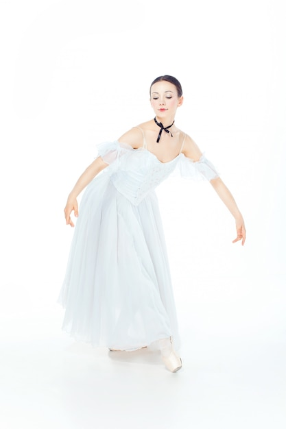 Ballerina in het witte kleding stellen op pointeschoenen, studiowit. Gratis Foto
