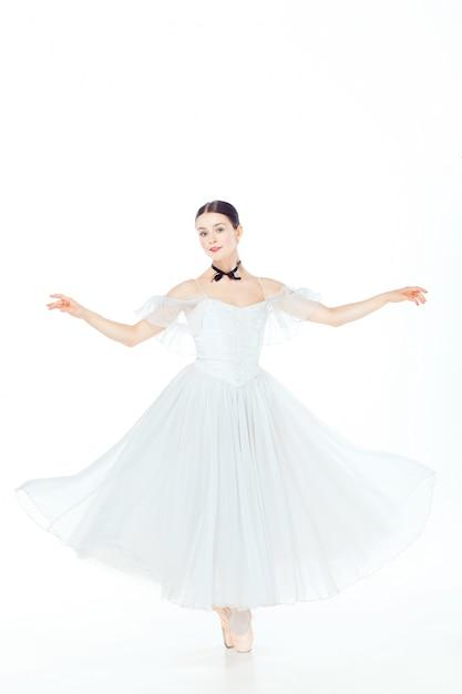 Ballerina in witte jurk poseren op pointe schoenen, studio ruimte. Gratis Foto