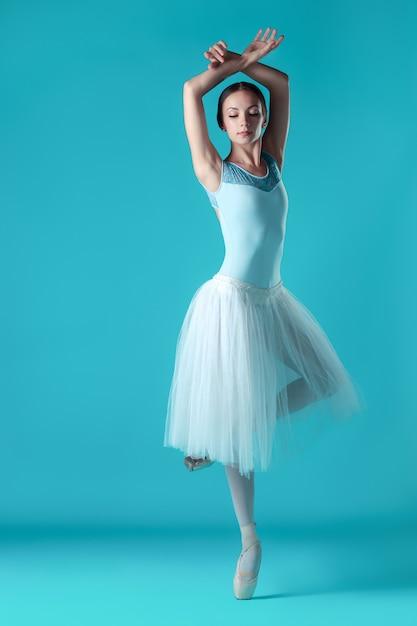 Ballerina in witte jurk poseren op tenen Gratis Foto