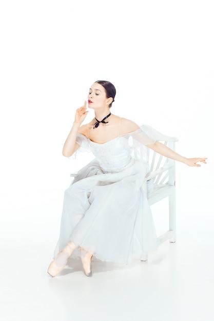 Ballerina in witte jurk zittend op een witte stoel, studio wit. Gratis Foto