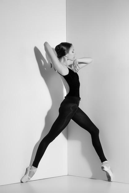 Ballerina in zwarte outfit poseren op pointe-schoenen Gratis Foto