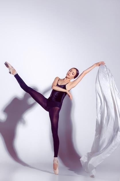 Ballerina in zwarte outfit poseren op tenen, studio achtergrond. Gratis Foto