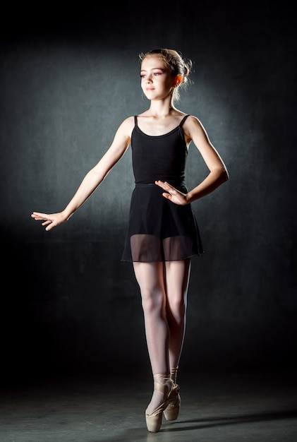 Ballerina. leuk meisje die en in studio stellen dansen. het meisje studeert ballet. donkere muur. Premium Foto