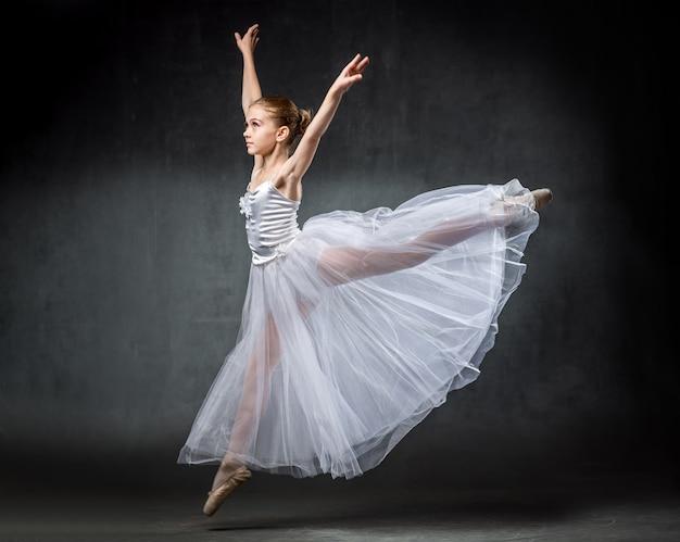 Ballerina. leuk meisje die en in studio stellen dansen. het meisje studeert ballet. . Premium Foto