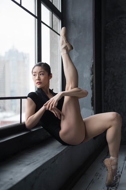 Ballerina poseren bij het raam met been omhoog Gratis Foto