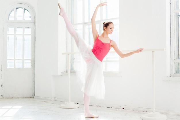 Ballerina poseren in pointe-schoenen op witte houten paviljoen Gratis Foto