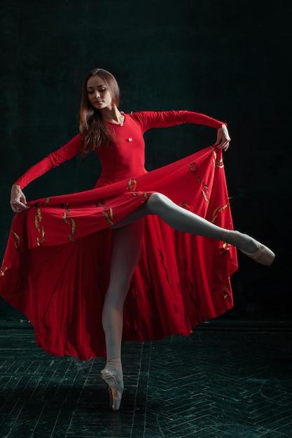 Ballerina poseren in pointe-schoenen op zwarte houten paviljoen Gratis Foto