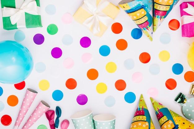 Ballonconfettien met geschenkdozen; feesthoed; toeter; beschikbare kop op witte achtergrond Gratis Foto
