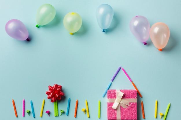 Ballonnen boven het huis gemaakt met geschenkdoos; kaarsen en rood lint buigen tegen blauwe achtergrond Gratis Foto