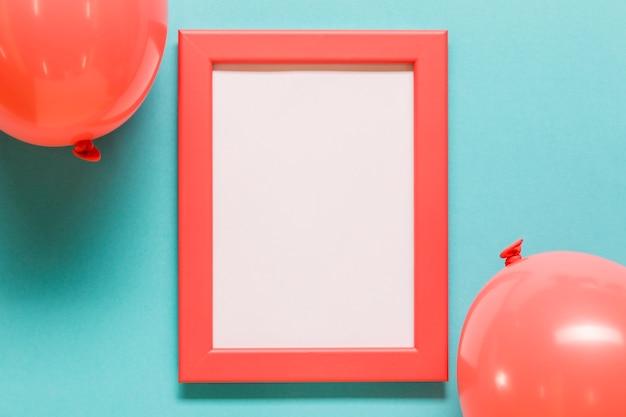 Ballonnen en leeg frame op blauwe achtergrond Gratis Foto