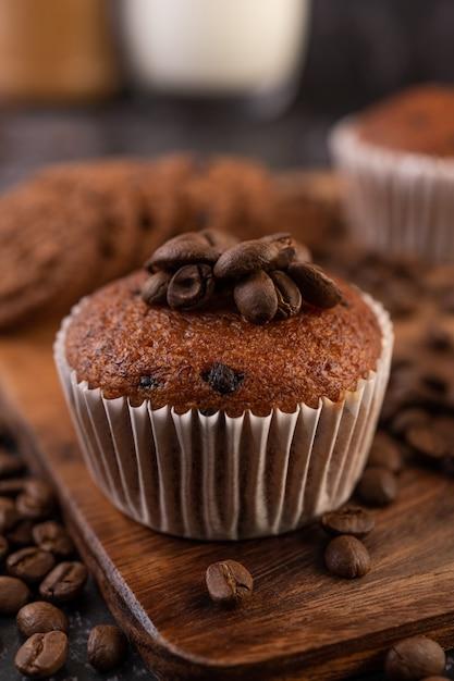 Banaan cupcakes die op een houten bord met koffiebonen worden geplaatst. Gratis Foto