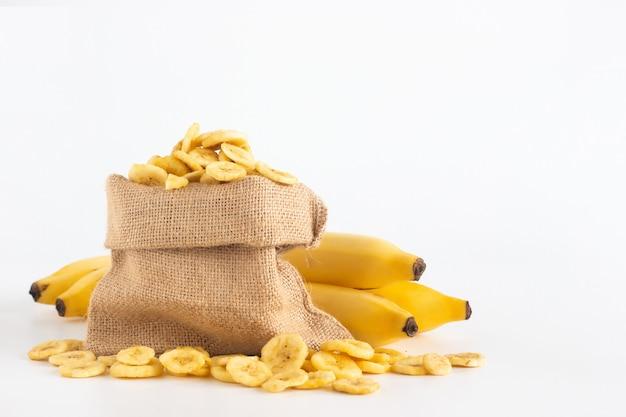 Banaan en gedroogde banaan segmenten in zak zak met kopie ruimte geïsoleerd op wit Premium Foto