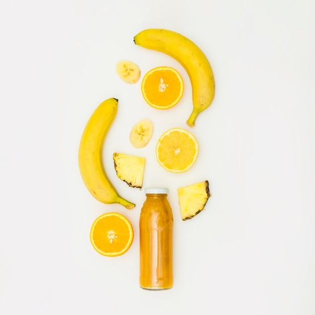 Banaan; gehalveerd oranje; plak ananas over de smoothiefles tegen witte achtergrond Gratis Foto
