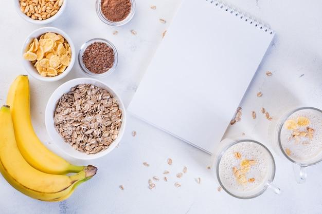 Banaan smoothie in kopjes, lijnzaad, cacao, havermout en gepofte rijst op een witte achtergrond. gezond eten concept Premium Foto